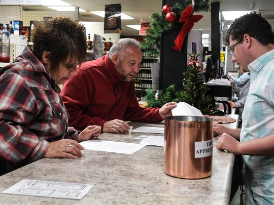 Mary Jo Phelps and David Flynn look over the beer list before having growlers filled by Matt Watson (right) at the Henderson Beverage Barn in store tasting bar Friday, December 16, 2016.