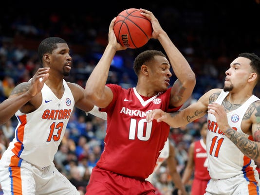 Arkansas' Daniel Gafford (10) tries to squeeze past Florida's Kevarrius Hayes (13) and Chris Chiozza (11) during the first half of an NCAA college basketball game in the quarterfinals of the Southeastern Conference tournament, Friday, March 9, 2018, in St. Louis. (AP Photo/Jeff Roberson)