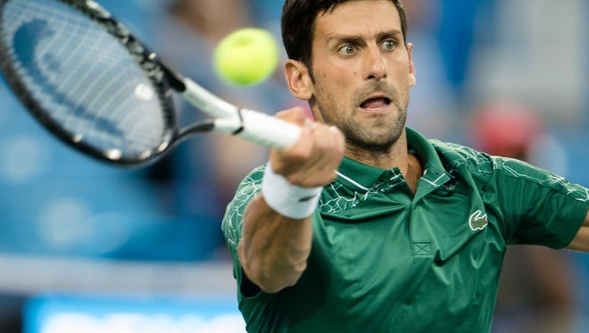 Novak Djokovic returns against Grigor Dimitrov during their match at the Western & Southern Open at the Lindner Family Tennis Center in Mason, Ohio, on Thursday, Aug. 16, 2018.