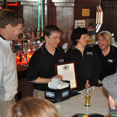 Green Bay Packers President Mark Murphy, left, presents a plaque honoring Edward Schuster to Jason Baugnet, Amanda Baugnet and Theresa Suster at the conclusion of the team's 10th annual Tailgate Tour. Edward Schuster was a 54-year member of the Packers board of directors and member of the family that owns Suster's Arcade in Denmark.