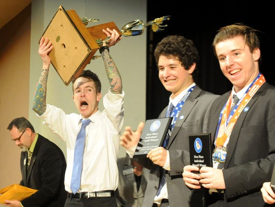 Calabasas High School coach Tyler Lee, left, picks up the trophy after the team won the title at Pacifica High School during the Ventura County Academic Decathlon awards ceremony last year.