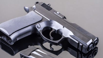 9 mm hand gun on glass table with reflection; Shutterstock ID 92949556; PO: aol; Job: production; Client: drone