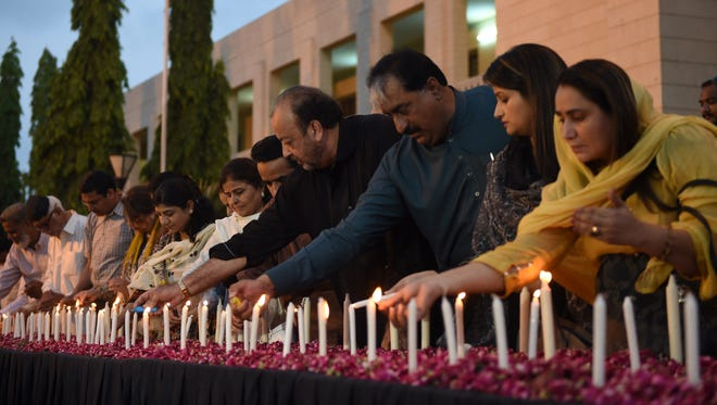 Pakistani legislators light candles during a vigil on May 14, 2015, for the victims of an attack by gunmen on a bus of Shiite Ismaili Shiite minority in Karachi.
