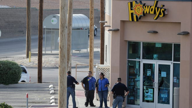 El Paso Police Department officers stand at the scene of a shooting and robbery along with employees of the store. The robbery took place Wednesday afternoon at the Howdy's gas staion at the intersection of McRae and Gateway West boulevards. No injuries were reported.