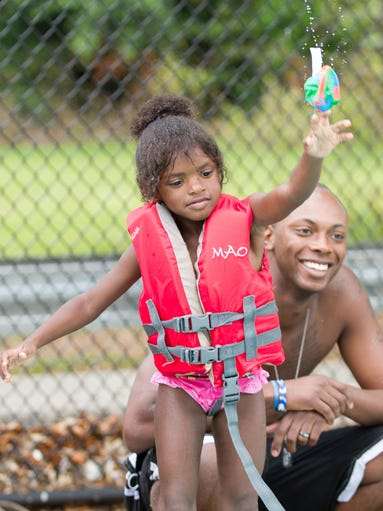 Imari James, 4, throws a ball while watched by her father, Jason Williams, at the Splash and Jam preview party at the Lawrence-Gregory Community Center on Wednesday, June 4, 2014 in Tallahassee, Fla.