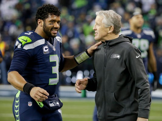 Seattle Seahawks quarterback Russell Wilson, left, talks with head coach Pete Carroll before an NFL divisional playoff football game against the Carolina Panthers in Seattle, Saturday, Jan. 10, 2015. (AP Photo/Elaine Thompson)