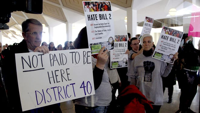 Anti-HB2 protesters hold signs in the Legislative Building in Raleigh Wednesday. The sign held by the man at left is a reference to apparently unsubstantiated charges that some protesters had been paid.