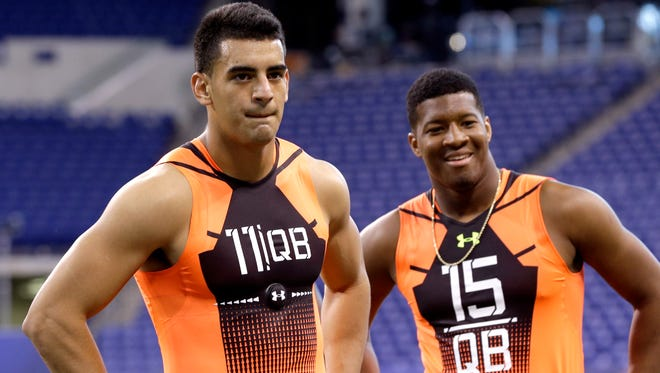 Oregon quarterback Marcus Mariota (11) and Florida State quarterback Jameis Winston (15) wait to run a drill at the NFL football scouting combine in Indianapolis, Saturday, Feb. 21, 2015.