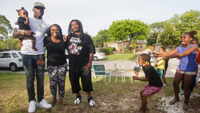 Jayron Kearse shares the joy of being drafted with his daughter Ja'riah, mother Danielle Anderson and stepfather Henry McClinton at his home Saturday in Fort Myers. Kearse was picked by the Minnesota Vikings.