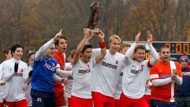 Mason players run to their fans as they celebrate with their Regional Championship trophy after a 1-0 win over Dearborn Divine Child Saturday, Oct. 31, 2015, in Mason, Mich.