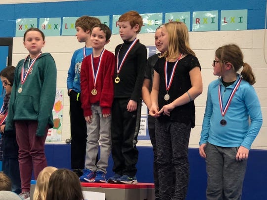 Third-graders stand on the podium with their medals at Riverside's Math Olympics.