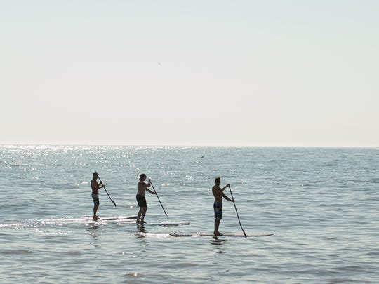 Beach-goers paddleboard off the coast of Rehoboth Beach on July 5. Of 428 people who drowned while recreational boating last year, 352 weren't wearing life jackets, according to the U.S. Coast Guard.