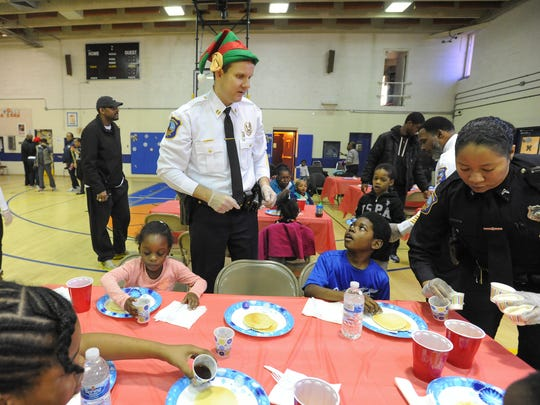 Capt. Stephen Misetic of the Wilmington Police Department talks with kids who came to eat breakfast that the Police Department cooked at West Center City's Hicks Anderson Center in 2015.