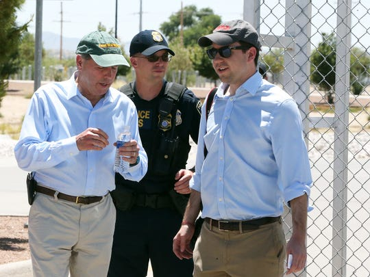 U.S. Senator Tom Udall, D-NM, left, walks out of the gates to the Marcelino Serna Port of Entry after visiting the area where undocumented immigrant children are housed Saturday.