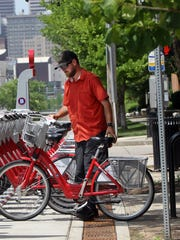 The Enquirer/Patrick Reddy Hayden Stone, a field technician for Bycycle Co., places a bicycles in a rack during a routine check of one of several Red Bike locations opened Tuesday in Covington. Hayden Stone, a field technician for Bycycle Co., places a bicycles in a rack during a routine check of one of several Red Bike locarions opened 6/23 in Covington.  The Enquirer/Patrick Reddy