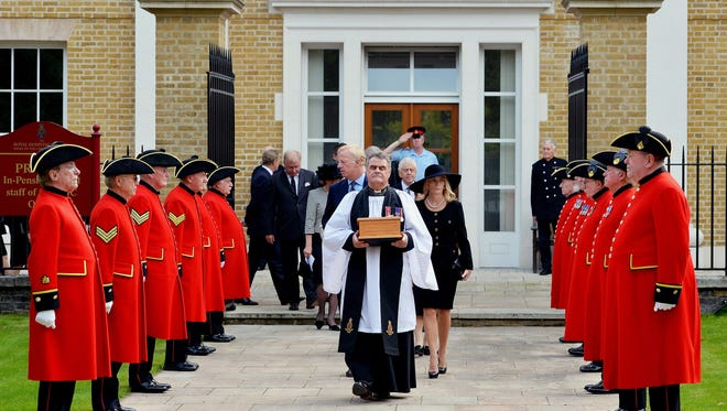 Reverend Richard Whittington, foreground center,  carries an oak casket containing the ashes of former British  Prime Minister Margaret Thatcher, followed by her daughter Carol, son Mark, center left  and his wife Sarah, center left,  after leaving the chapel,  at the Royal Hospital Chelsea, London.