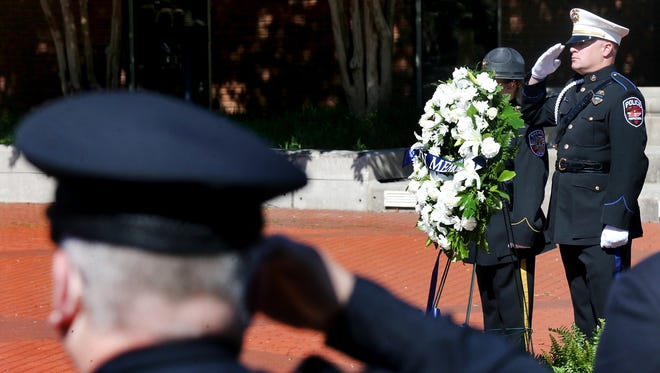 Murfreesboro police officer Mark Todd with the Honor Guard salutes next to the wreath placed for the Rutherford County fallen officers as members of other police agency honor guard units salute during a ceremony held at the Civic Plaza.