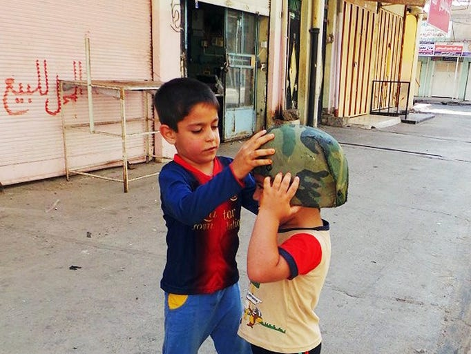 Children play with an Iraqi Army helmet on June 13, 2014, left behind after militants from the al-Qaeda-inspired Islamic State of Iraq and the Levant (ISIL) took over the northern city of Mosul, Iraq.