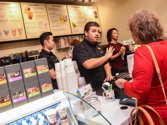 Barista Mark Alex, center, takes an order from a customer during the official grand opening of Archway, Inc.'s latest Infusion Coffee & Tea location, inside the T Galleria by DFS, Guam in Tumon, on Friday, March 23, 2018. The food outlet is the eighth store to join the franchise chain that started with its first location which opened in upper Tumon in June 2009, said Mika Gibson, Archway vice president.