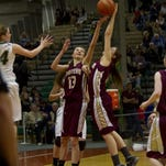 Choteau's Molly Salmond (#12) and Tristin Achenbach (13) leap after a rebound during the Bulldogs' semifinal loss to Colstrip in the 2015 State B basketball tournament. A year later, Choteau has just seven high school girls out for basketball and eighth-graders are filling in for the Bulldogs.