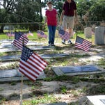 Sylvia Burgen and Jerry Addleman walk past grave markers that have been adorned with American flags at Veterans Cemetery in Titusville. Several groups combined to help set the flags ahead of Memorial Day.