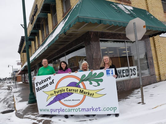 Jim Weiss, Susy Prosapio, Cathy Hartle and Darlene hold a sign at the future location of the Purple Carrot Market Friday, March 30, in Little Falls.