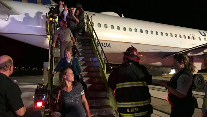 Passengers walk down emergency stairs from the rear of Reno-bound United Airlines flight 296 on Sept. 19 at Denver International Airport. Passengers loaded into buses to be taken back to the airport terminal so they could get onto a new airplane.