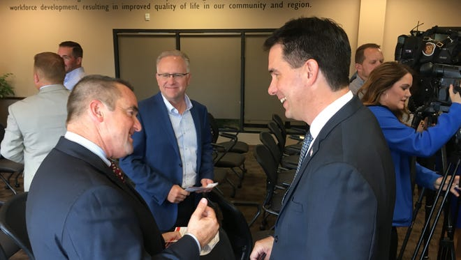 Green Bay Mayor Jim Schmitt and Gov. Scott Walker talk after Walker rolled out a four-part plan he says will help bolster small businesses.