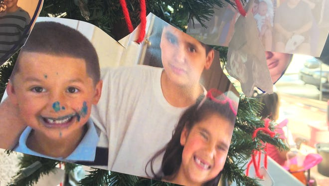 A picture of Eddie Vargas with his siblings hanging from a Christmas tree at a car wash in west Phoenix held to raise funds for the teen's funeral.