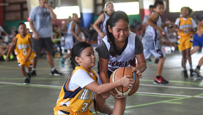 In this June 30 file photo, Yellowjackets Yellow player Jaedin White battles for the ball against the Crusaders' Jaelyn Han during a Guam Youth Basketball Association Drug Free League game at Astumbo Gym.