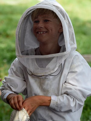 Lincoln Adkins 7, suits up before handling bees at Trevecca's Urban Farm on July 20, 2016.