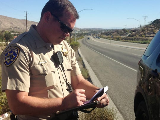 California Highway Patrol Officer Jesse Miller writes a ticket on the side of Highway 62 during a patrol on Oct. 22. Miller, who has worked in the High Desert for six years, believes the highway has an increased risk of broadside collisions and single-car rollovers.