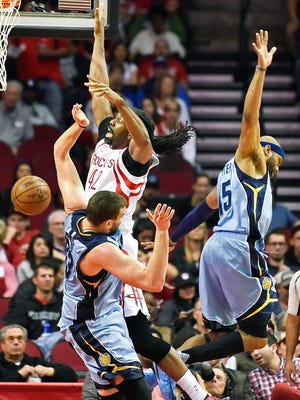 Houston Rockets center Nene Hilario (42) is fouled by Memphis Grizzlies center Marc Gasol, bottom, as guard Vince Carter defends in the first half of an NBA basketball game, Saturday, March 4, 2017, in Houston.
