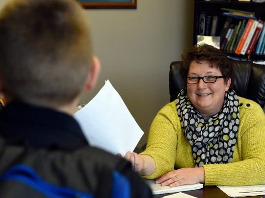 Resurrection School principal Theresa Berendes accepts a paper from seventh grader Kenton Kissel in her office at the school last year.  Berendes was selected as an outstanding principal finalist this year and last.