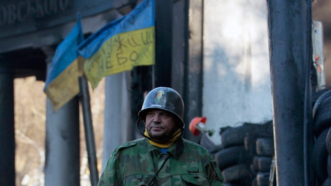 A protester guards a barricade in front of riot police in Kiev on Thursday.