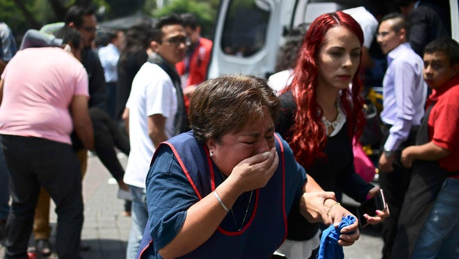 People react after a real quake rattled Mexico City on Sept. 19, 2017 moments after an earthquake drill was held in the capital.