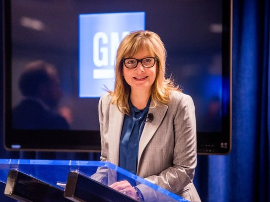 Barra is shown standing at a podium in front of a lighted GM logo.