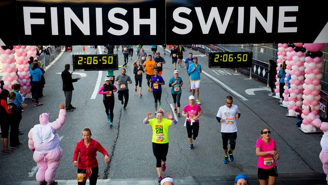 Half marathon runners cross the Finish Swine at the 19th annual Flying Pig Marathon Sunday, May 7, 2017 in Cincinnati.