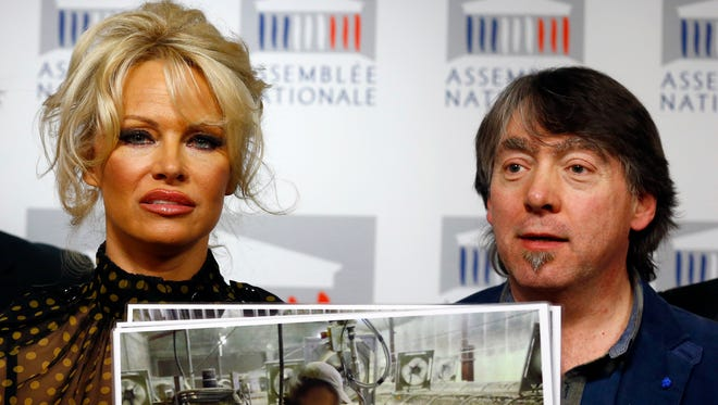 Pamela Anderson, actress and animals rights defender, left, displays photos with head of Global Action in the Interest of Animals (GAIA) Michel Vandenbosch during a news conference at the French National Assembly to protest the force-feeding of geese used in the production of foie gras, in Paris, France, Tuesday, Jan. 19, 2016.