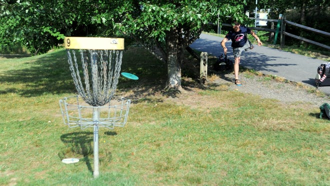 A tree makes for a difficult putt on the ninth hole of the disc golf course at Veterans Park on July 4.