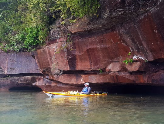 Steve Jones kayaks under some sandstone cliffs on Manitou