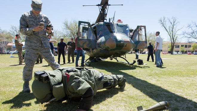 Nicholas Rodriguez, right, a New Mexico State University Air Force ROTC cadet, performs push-ups in a bomb suit , while fellow cadet Armando Alvarez, left, films him Thursday March 29, 2018 at the Horseshoe at NMSU, during the NMSU Air Force ROTC's A&M Day.