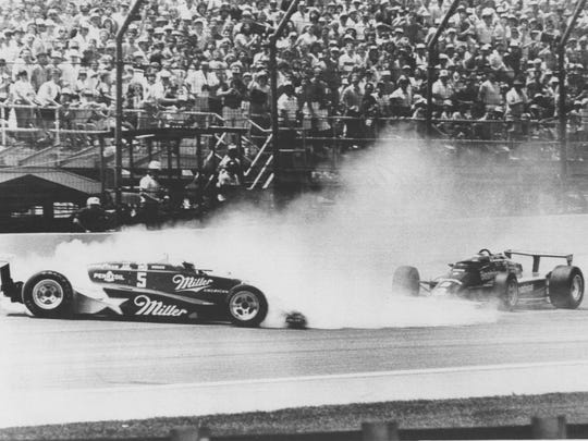 Mario Andretti (r) heads for the bottom of the track to avoid spin by Danny Sullivan (l) coming out of the first turn, 5/27/1985.
