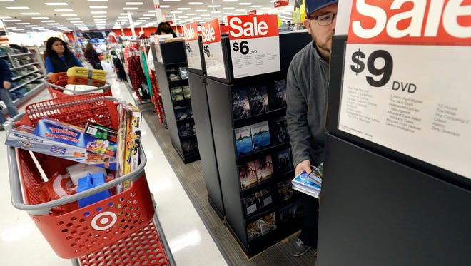 Paul Poirier shops at a Target store, in Wilmington, Mass. Target is lowering its fourth-quarter profit and sales outlook after the discounter said that sluggish holiday sales and traffic in its stores offset a surging online business.