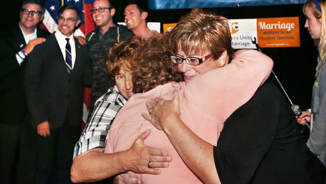 "IMPD Officer Teresa Welborn, left, and her spouse Beth Piette, right (they were married in Hawaii in 2013) get a hug at the Hoosiers Unite for Marriage ""Love Wins"" celebration on Oct. 6, 2014."
