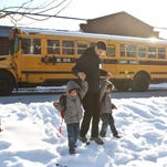 Mostafa Abdelrahman holds the hands of Mohamed, left, and Zyad, right, while crossing the street after school dismissal at Cochran Elementary in Old Louisville Friday. A glut of snow days is forcing school districts in Kentucky and Indiana to consider some radical options to make up for the lost class time.