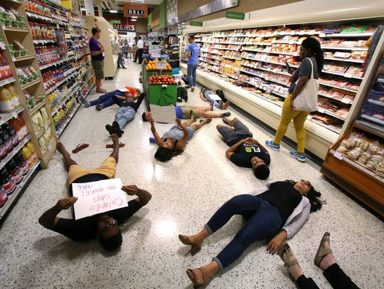 Demonstrators lay on the floor during a protest against