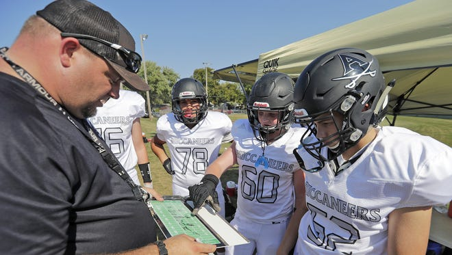 Allouez Buccaneers 8th grade team coach Matt Bumgardner coaches his defense during their game Saturday, September 23, 2017 at Webster Park in Allouez, Wis. Their uniforms were purchased by Packers quarterback Brett Hundley.