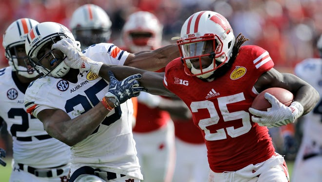 Wisconsin running back Melvin Gordon (25) stiff-arms Auburn defensive back Jermaine Whitehead (35) on a 53-yard touchdown run during the third quarter of the Outback Bowl college football game on Thursday in Tampa, Fla.