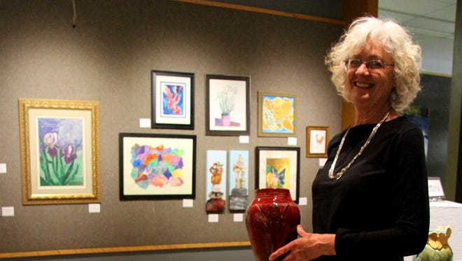 Show chairwoman Janice May shows off one of her pottery creations at the Carlsbad Museum and Art Center.